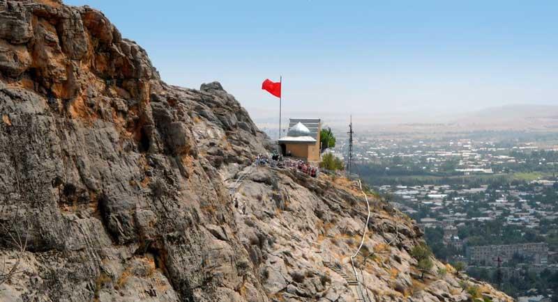 тахт-и Сулейман на фоне горы и города Ош